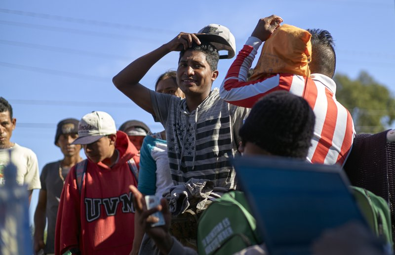 Migrants from Central America line up to begin the process of returning to their countries with the help of the International Organization of Migration outside a shelter set up for members of the migrant caravan Monday, Nov. 26, 2018, in Tijuana, Mexico. A day after a march by members of the migrant caravan turned into an attempt to breach the U.S. border with Mexico, many migrants appeared sullen, wondering whether the unrest had spoiled whatever possibilities they might have had for making asylum cases. (AP Photo/Gregory Bull)