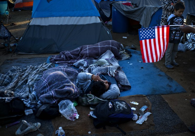 A migrant holding a U.S. flag, right, speaks with others waking up at the Benito Juarez Sports Center that's serving as a temporary shelter in Tijuana, Mexico, early Monday, Nov. 26, 2018. The mayor of Tijuana has declared a humanitarian crisis in his border city and says that he has asked the United Nations for aid to deal with thousands of Central American migrants who have arrived in the city. (AP Photo/Ramon Espinosa)