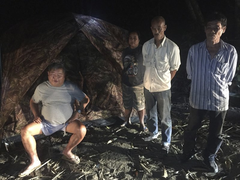File-In this Feb. 4, 2018, file photo, photo released by the Thailand Department of National Parks, Wildlife and Plant Conservation, the president of Thailand's largest construction company Premchai Karnasuta, 63, left, is seen with a group while being detained in the Thungyai Naresuan Wildlife Sanctuary in Kanchanaburi province on Thailand's western border. The trial has begun for Premchai who is accused of poaching an endangered black panther and other animals. (Thailand Department of National Parks, Wildlife and Plant Conservation via AP, File)