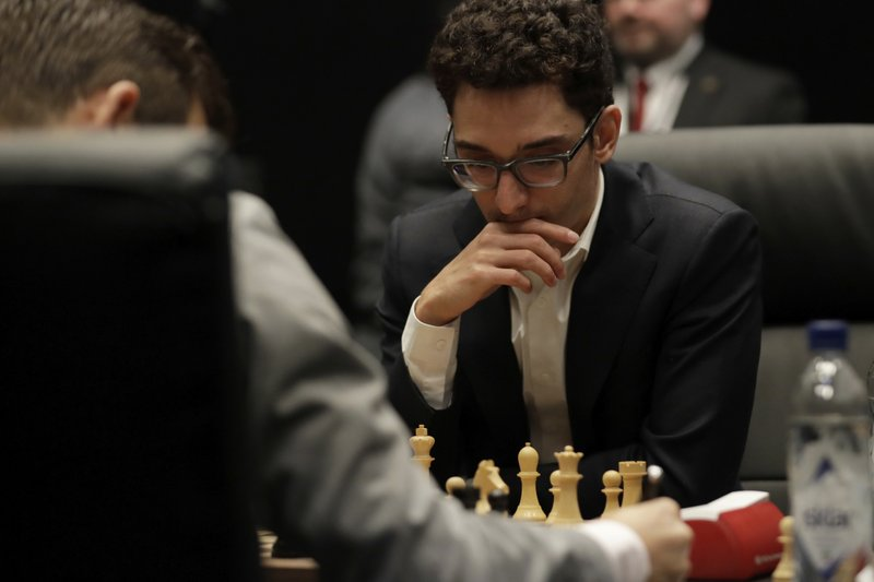 Italian-American challenger Fabiano Caruana plays reigning chess world champion Magnus Carlsen, left, from Norway, in the first few minutes of round 12 of their World Chess Championship Match in London, Monday, Nov. 26, 2018. (AP Photo/Matt Dunham)