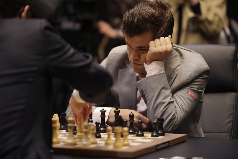 Reigning chess world champion Magnus Carlsen, from Norway, plays Italian-American challenger Fabiano Caruana, left, in the first few minutes of round 12 of their World Chess Championship Match in London, Monday, Nov. 26, 2018. (AP Photo/Matt Dunham)