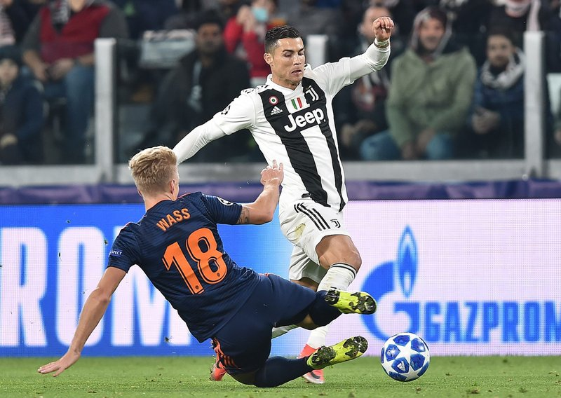 Juventus' Cristiano Ronaldo is tackled by Valencia' Daniel Wass during the Champions League group H soccer match between Juventus and Valencia at the Allianz stadium in Turin, Italy, Tuesday, Nov. 27, 2018