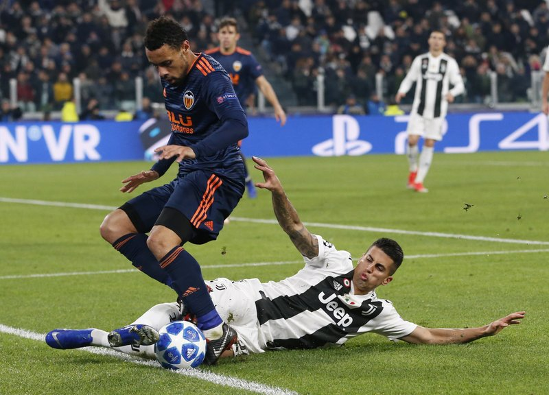 Juventus defender Joao Cancelo, right, challenges for the ball with Valencia midfielder Francis Coquelin during the Champions League group H soccer match between Juventus and Valencia at the Allianz stadium in Turin, Italy, Tuesday, Nov. 27, 2018. (AP Photo/Antonio Calanni)