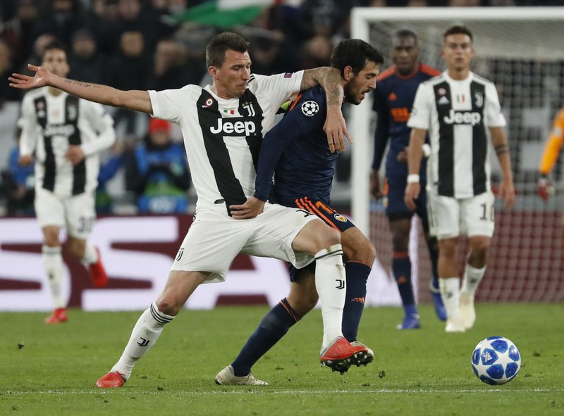 Juventus forward Mario Mandzukic, left, challenges for the ball with Valencia midfielder Daniel Parejo during the Champions League group H soccer match between Juventus and Valencia at the Allianz stadium in Turin, Italy, Tuesday, Nov. 27, 2018. (AP Photo/Antonio Calanni)