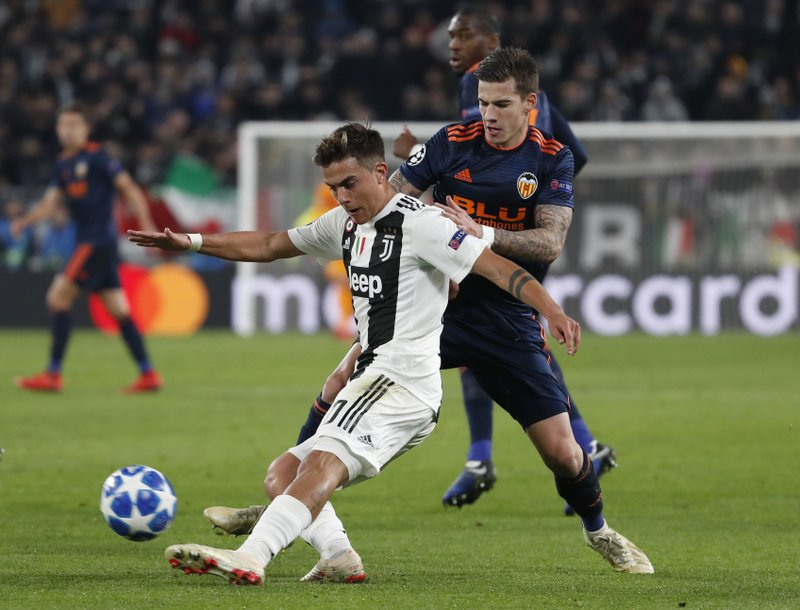 Juventus forward Paulo Dybala, left, challenges for the ball with Valencia forward Santi Mina during the Champions League group H soccer match between Juventus and Valencia at the Allianz stadium in Turin, Italy, Tuesday, Nov. 27, 2018. (AP Photo/Antonio Calanni)