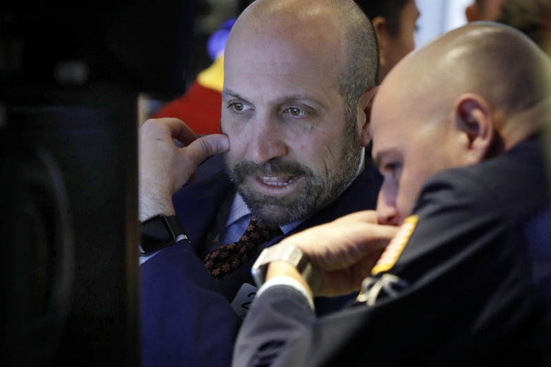Specialists James Denaro, left, and Mario Picone huddle at a trading post on the floor of the New York Stock Exchange, Wednesday, Nov. 28, 2018. Stocks are opening higher on Wall Street, led by solid gains in big technology and health care companies. (AP Photo/Richard Drew)