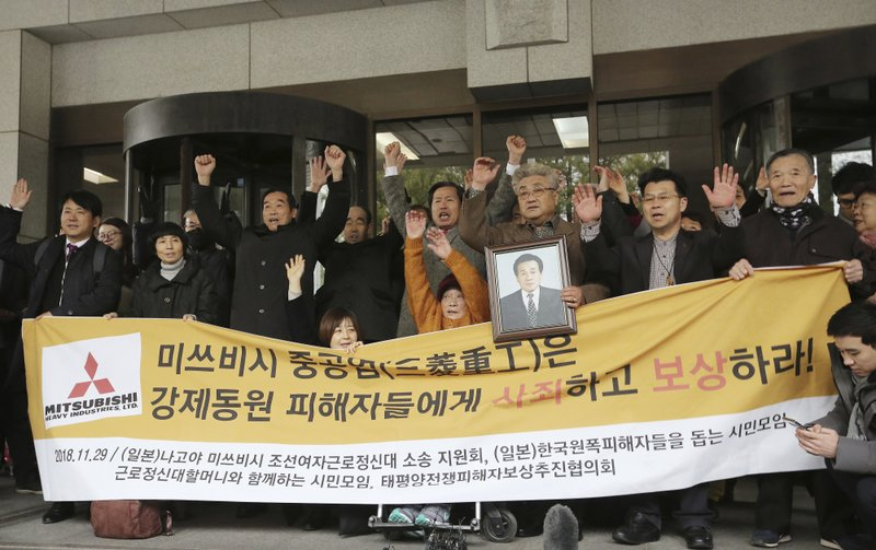 Korean victims of Japan's forced labor and their family members raise their hands in celebration after the Supreme Court's ruling ordering Japan's Mitsubishi Heavy Industries to compensate them in Seoul, South Korea, Thursday, Nov. 29, 2018. South Korea's top court has ordered a Japanese company to compensate 10 Koreans for forced labor during Tokyo's 1910-45 colonial rule of the Korean Peninsula. The signs read: