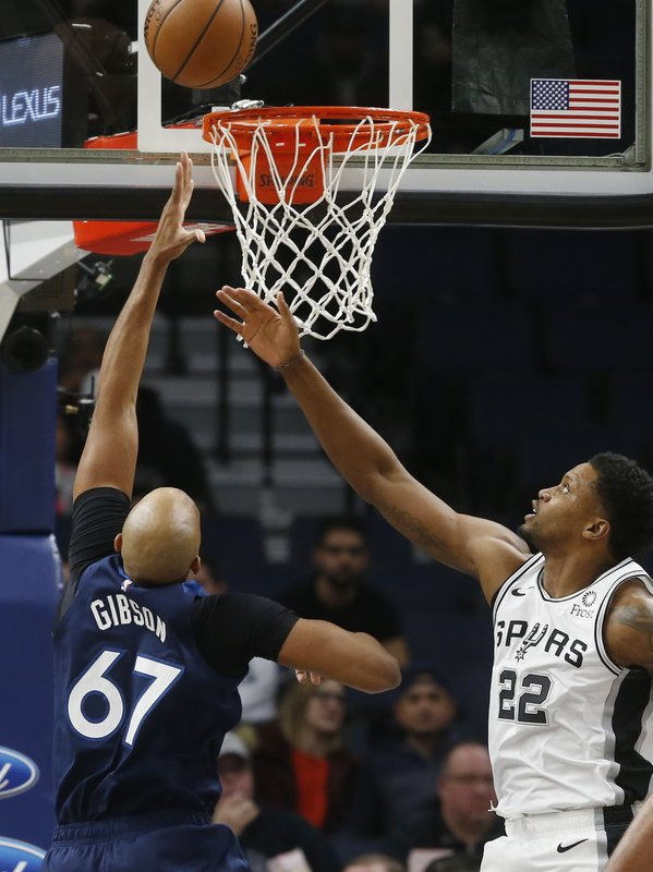 Minnesota Timberwolves' Taj Gibson, left, lays up as San Antonio Spurs' Rudy Gay watches in the first half of an NBA basketball game Wednesday, Nov. 28, 2018, in Minneapolis. (AP Photo/Jim Mone)