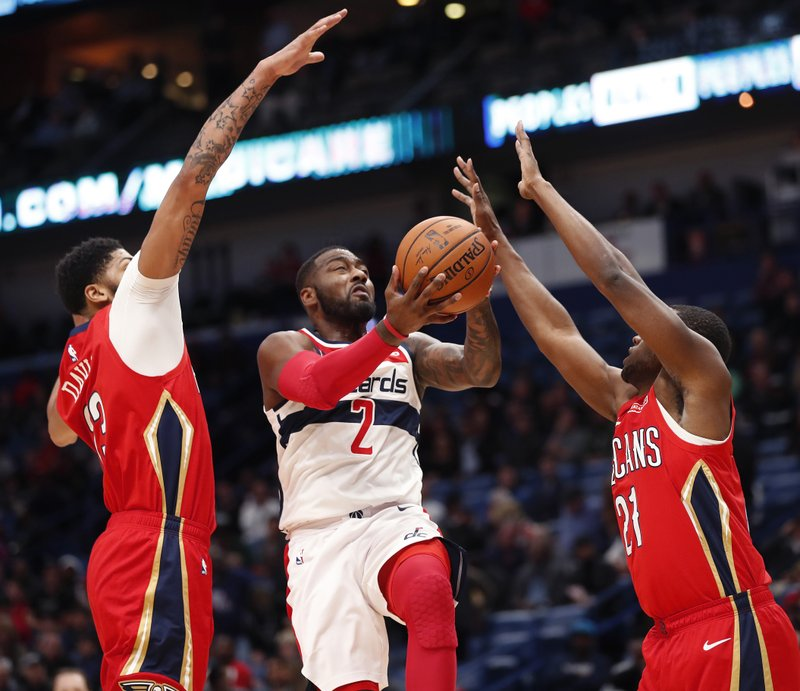 Washington Wizards guard John Wall (2) goes to the basket betweenNew Orleans Pelicans forward Anthony Davis (23) and forward Darius Miller (21) in the first half of an NBA basketball game in New Orleans, Wednesday, Nov. 28, 2018. (AP Photo/Gerald Herbert)