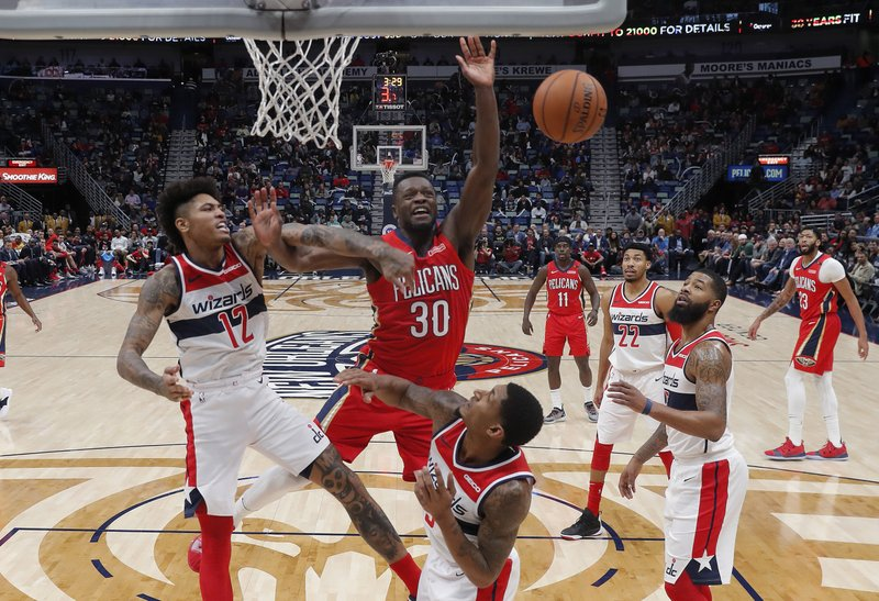 Washington Wizards forward Kelly Oubre Jr. (12) battles under the basket with New Orleans Pelicans forward Julius Randle (30) in the first half of an NBA basketball game in New Orleans, Wednesday, Nov. 28, 2018. (AP Photo/Gerald Herbert)