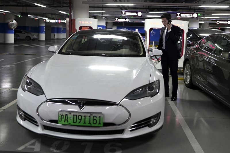 In this Wednesday, Sept. 12, 2018, photo, An Baojia, right, makes a phone call near his Tesla vehicle at a charging station in Shanghai. More than 200 manufacturers, including Tesla, Volkswagen, BMW, Daimler, Ford, General Motors, Nissan, Mitsubishi and U.S.-listed electric vehicle start-up NIO, transmit position information and dozens of other data points to Chinese government-backed monitoring centers, The Associated Press has found. Generally, it happens without car owners' knowledge. (AP Photo)