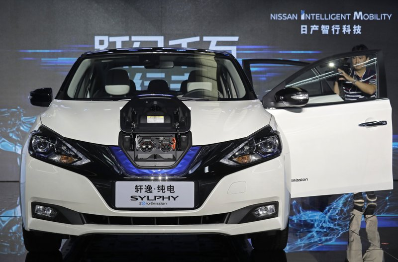FILE - In this Aug. 27, 2018, file photo, a cameraman takes video of a Nissan Sylphy Zero Emission, the Nissan's first all-electric vehicle built in China, at the Nissan factory in Guangzhou, Guangdong province, China. More than 200 manufacturers, including Tesla, Volkswagen, BMW, Daimler, Ford, General Motors, Nissan, Mitsubishi and U.S.-listed electric vehicle start-up NIO, transmit position information and dozens of other data points to government-backed monitoring centers, The Associated Press has found. Generally, it happens without car owners' knowledge. (AP Photo/Vincent Yu, File)