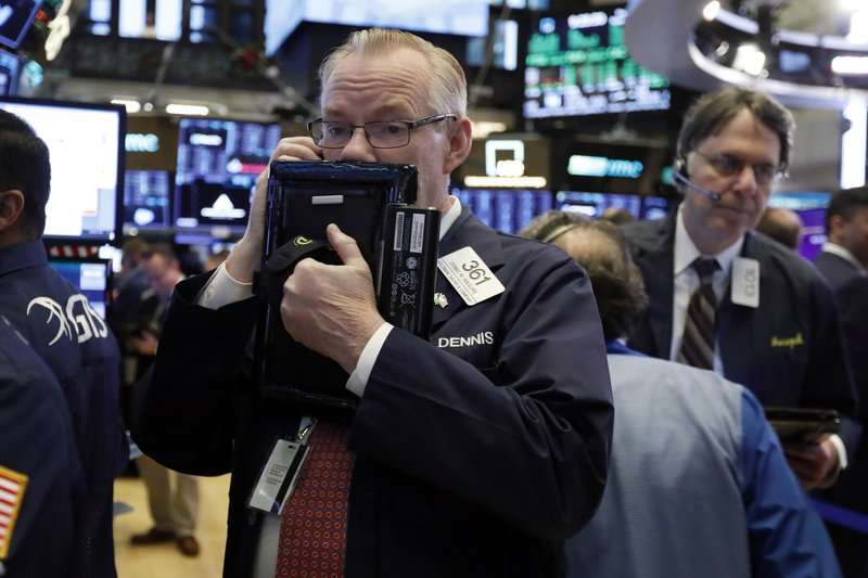 Trader Dennis Maguire, left, works on the floor of the New York Stock Exchange, Thursday, Nov. 29, 2018. U.S. stocks are lower Thursday morning after huge gains the day before. (AP Photo/Richard Drew)