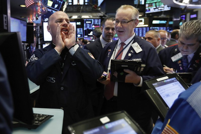 Specialist John O'Hara, left, works with traders at his post on the floor of the New York Stock Exchange, Thursday, Nov. 29, 2018. U.S. stocks are lower Thursday morning after huge gains the day before. (AP Photo/Richard Drew)