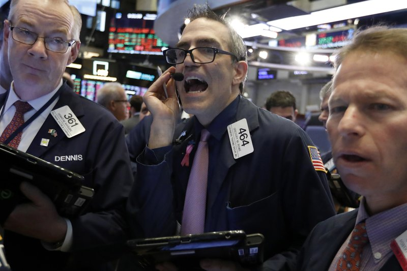 Trader Gregory Rowe, center, works on the floor of the New York Stock Exchange, Thursday, Nov. 29, 2018. U.S. stocks are lower Thursday morning after huge gains the day before. (AP Photo/Richard Drew)