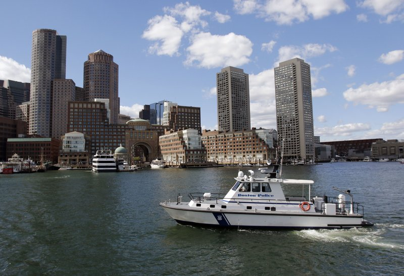 FILE- In this Sept. 24, 2016 file photo, a Boston Police Department boat patrols in Boston Harbor. A canary in a coal mine? How about a flounder in a harbor? Offering a rare bit of good environmental news, scientists have documented a dramatic rebound in fish health they say shows how once horribly polluted Boston Harbor has cleaned up its act. (AP Photo/Bill Sikes, File)