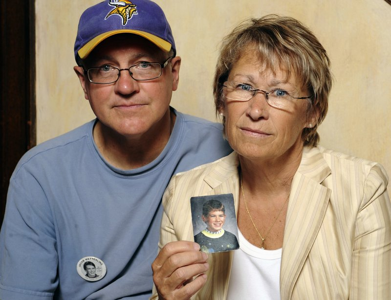 FILE - In this Aug. 28, 2009, file photo, Patty and Jerry Wetterling show a photo of their son Jacob Wetterling, who was abducted in October 1989 in St. Joseph, Minn and was still missing, in Minneapolis. Daniel Heinrich, of Minnesota, who confessed to kidnapping, sexually assaulting and killing Jacob, also molested Jared Scheierl months before Jacob was abducted from a rural road near his home. On Thursday, Nov. 29, 2018, Scheierl was awarded more than $17 million in damages. In 2016, Heinrich admitted to sexually assaulting Scheierl and to abducting, molesting and killing Jacob as part of a plea deal in a federal child pornography case. (AP Photo/Craig Lassig, File)
