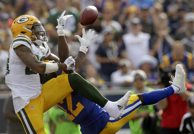 "FILE - In this Oct. 28, 2018, file photo, Green Bay Packers cornerback Jaire Alexander, left, breaks up a pass intended for Los Angeles Rams wide receiver Brandin Cooks during the first half of an NFL football game in Los Angeles. Alexander, who was seven when Arizona Cardinals' Larry Fitzgerald broke into the league 15 seasons ago, might have to cover the veteran this week. ""So I mean it's pretty wild to think about it. But I've got my young legs under me so I'm good,"" Alexander said. (AP Photo/Marcio Jose Sanchez, File)"
