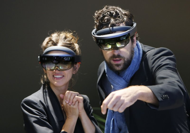 FILE- In this Sept. 24, 2017, file photo people use Microsoft Hololens to get an impression of Mercedes accessories on the stand of Mercedes-Benz during the first media day of the International Frankfurt Motor Show IAA in Frankfurt, Germany. Federal contract records show the U.S. Army has awarded Microsoft a $480 million contract to supply its HoloLens headsets to soldiers. The head-mounted displays use augmented reality, which means viewers can see virtual imagery superimposed over the real-world scenery in front of them. Microsoft says the technology will provide troops with better information to make decisions. (AP Photo/Michael Probst, File)