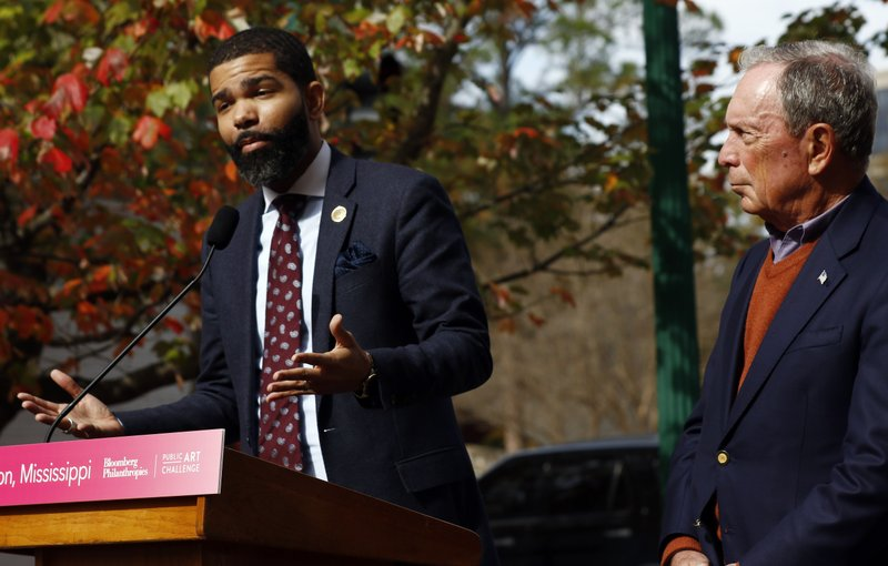 Former mayor of New York City, Michael R. Bloomberg, right, listens as Jackson Mayor Chokwe Antar Lumumba, responds to the city being named the winner of the Bloomberg Philanthropies 2018 Public Art Challenge winner, Thursday, Nov. 29, 2018. The city will receive a grant up to $1 million for a public art project addressing nutrition and food equity in Mississippi. (AP Photo/Rogelio V. Solis)