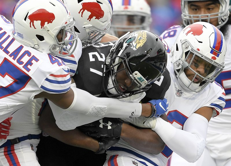 FILE - In this Nov. 25, 2018, file photo, Jacksonville Jaguars running back Leonard Fournette (27) is tackled by Buffalo Bills defenders during the first half of an NFL football gam in Orchard Park, N.Y. The surging Indianapolis Colts have averaged a little more than 33 points over their last eight games while the reeling Jaguars have topped 21 points once in the last two months. (AP Photo/Adrian Kraus, File)