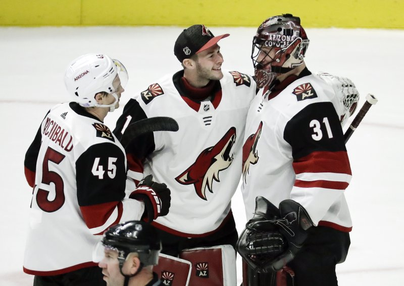 Arizona Coyotes goaltender Adin Hill (31) is congratulated by Josh Archibald (45) and Hunter Miska (1) after Hill shut out the Nashville Predators 3-0 in an NHL hockey game Thursday, Nov. 29, 2018, in Nashville, Tenn. (AP Photo/Mark Humphrey)
