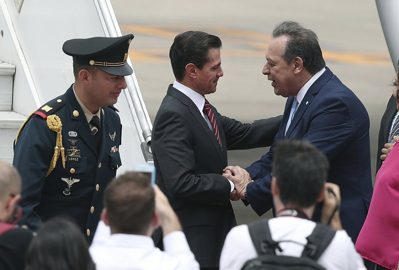 Mexico's President Enrique Pena Nieto, center, is received by Argentina's Tourism Secretary, Gustavo Santos, at the Ministro Pistarini international airport in Buenos Aires, Argentina, Thursday, Nov. 29, 2018. Leaders from the Group of 20 industrialized nations, including Pena Nieto, will meet in Buenos Aires for a two-day starting Friday. (AP Photo/Martin Mejia)