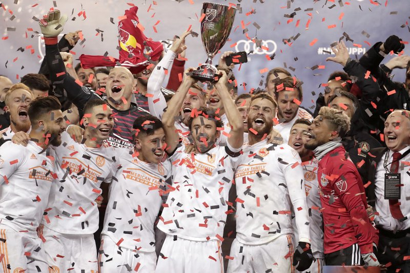 Atlanta United defender Michael Parkhurst, center, holds the Eastern Conference trophy after the team won the MLS soccer Eastern Conference championship Thursday, Nov. 29, 2018, in Harrison, N.J. The Red Bulls won Thursday's game 1-0, but Atlanta won 3-1 on aggregate. (AP Photo/Julio Cortez)