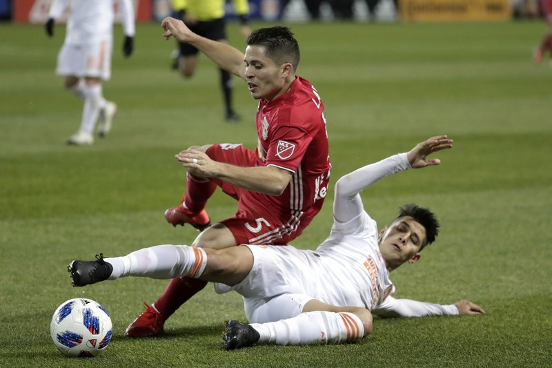 Atlanta United defender Franco Escobar, bottom, fouls New York Red Bulls defender Connor Lade during the second half of the second leg of the MLS soccer Eastern Conference championship Thursday, Nov. 29, 2018, in Harrison, N.J. The Red Bulls won 1-0, but Atlanta United won 3-1 on aggregate. (AP Photo/Julio Cortez)