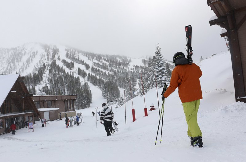 Skiers and snowboarders walk to the lifts at Mt. Rose Ski Tahoe Thursday, Nov. 29, 2018, near Reno, Nev. More than a foot (30 centimeters) of snow has fallen at some ski resorts around Lake Tahoe. The first of a series of storms moving into the Sierra dropped 14 inches (35 cm) at the Mt. Rose Ski Resort between Reno and Tahoe early Thursday. (Jason Bean/The Reno Gazette-Journal via AP)