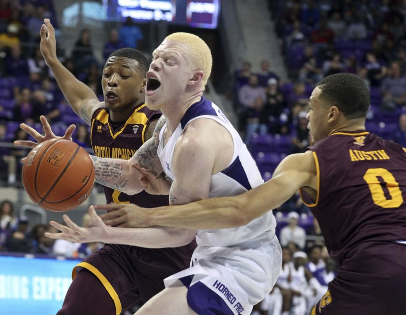 TCU guard Jaylen Fisher (10) tries to drive the ball between Central Michigan guard Shawn Roundtree (2) and guard Larry Austin Jr. (0) during the first half of an NCAA basketball game Friday, Nov. 30, 2018, in Fort Worth, Texas. (AP Photo/Richard W. Rodriguez)