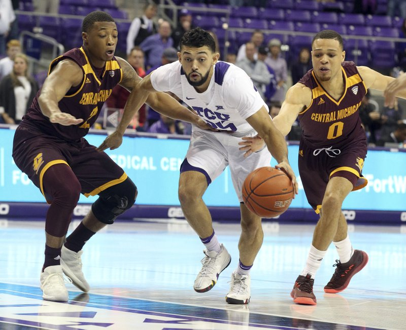 TCU guard Alex Robinson (25) drives the ball between Central Michigan guards Shawn Roundtree (2) and Larry Austin Jr. (0) during the first half of an NCAA college basketball game Friday, Nov. 30, 2018, in Fort Worth, Texas. (AP Photo/Richard W. Rodriguez)