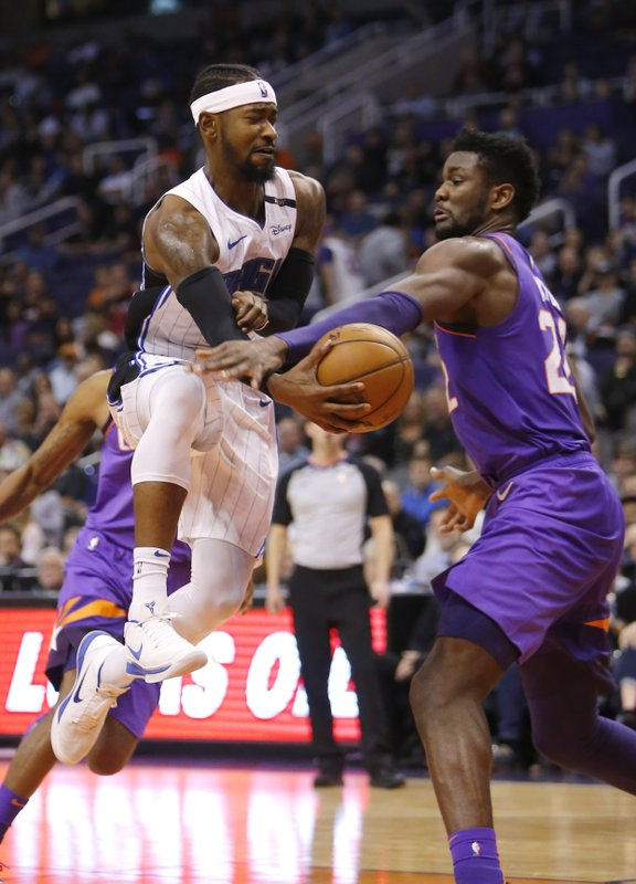 Orlando Magic guard Terrence Ross passes the ball around Phoenix Suns center Deandre Ayton (22) during the first half of an NBA basketball game Friday, Nov. 30, 2018, in Phoenix. (AP Photo/Rick Scuteri)