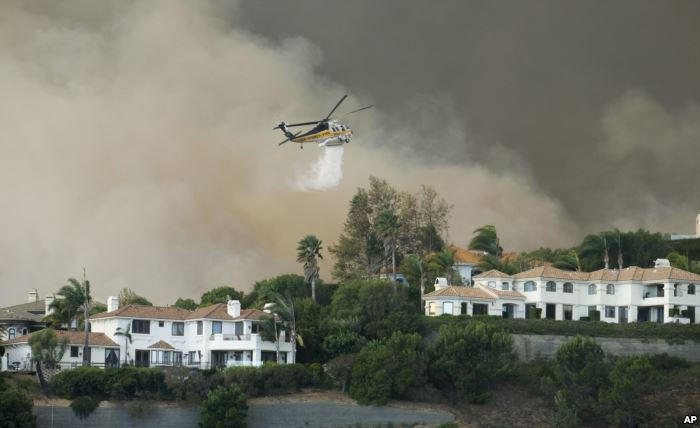 A helicopter drops water on a brush fire behind homes during the Woolsey Fire