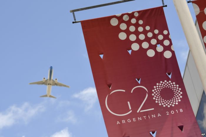 A jet liner flies over the G-20 summit venue at the Costa Salguero Center in