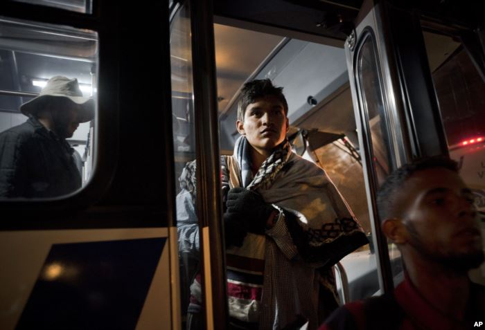 Central American migrants arrive in a bus at a shelter for migrants in Tijuan