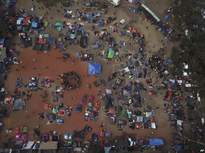 Central American migrants gather in an area designated for them to set up the