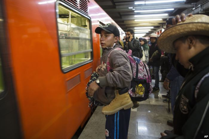 Central American migrants stand waiting for a subway car after leaving the te