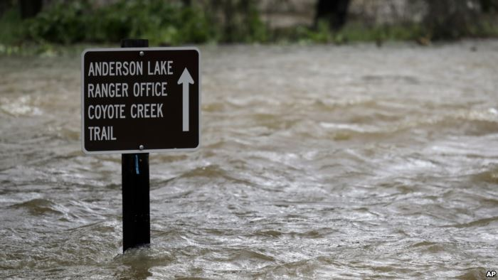 FILE - A sign is submerged in the water from Coyote Creek, Feb. 21, 2017, in