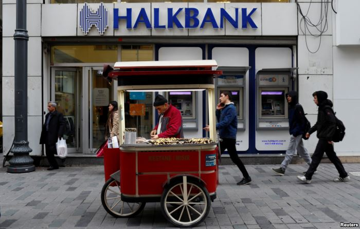 FILE - A street vendor sells roasted chestnuts in front of a branch of Halkba