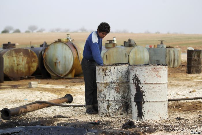 FILE - A youth works at a makeshift oil refinery in Syria, Dec. 16, 2015.