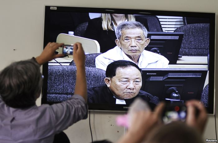 FILE - Journalists take photographs of a television screen showing the trial
