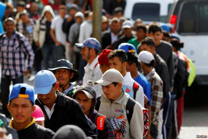 FILE - Migrants, part of a caravan of thousands trying to reach the U.S., sta