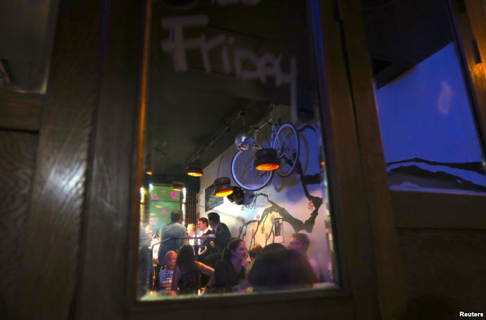 FILE - Patrons are reflected in a mirror as they drink at the York Lane Bar l