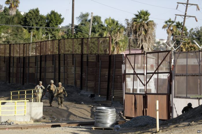Marines patrol during work to fortify the border structure that separates Tij