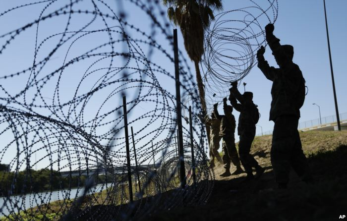 Members of the U.S. military install multiple tiers of concertina wire along