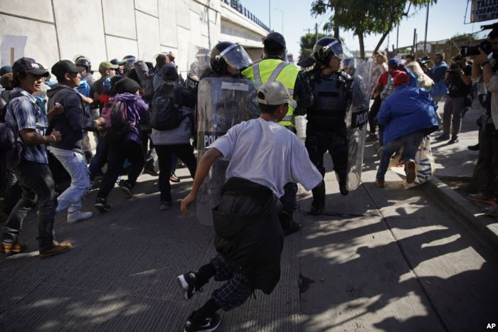 Migrants break past a line of police as they run toward the Chaparral border