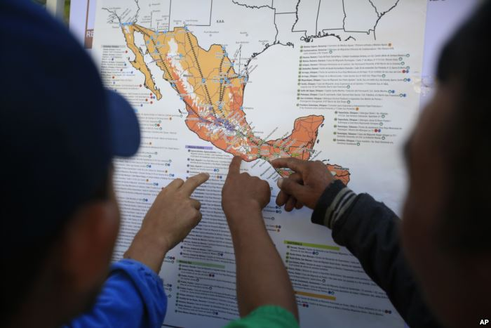 Migrants discuss their journey using a map posted inside the sports complex w