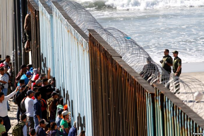 Migrants, part of a caravan of thousands trying to reach the U.S., look throu