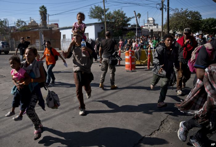 Migrants run toward the U.S. after breaking past a line of Mexican police at